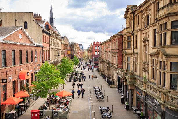Shoppers and other pedestrians walking through a street in Leeds, West Yorkshire stock photo