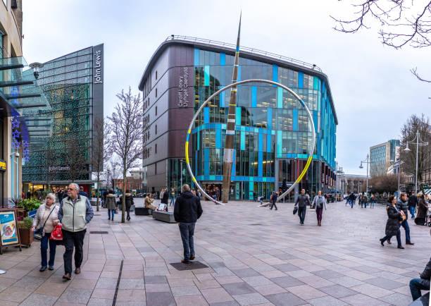 走在威爾士首都卡迪夫市中心國旗船威爾士約翰·路易斯商店和卡迪夫圖書館旁的購物者和遊客 - john lewis 個照片及圖片檔