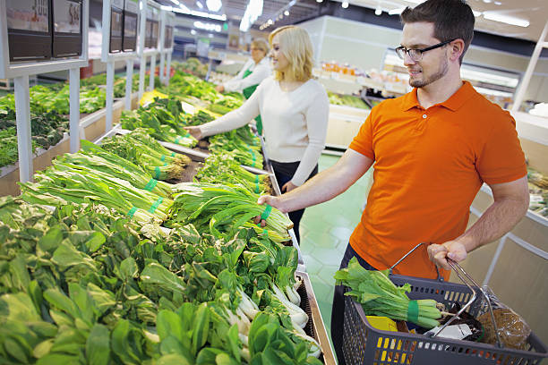 shoppers in grocery store selecting vegetables - chinakohlsalat stock-fotos und bilder