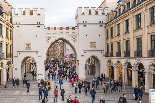 Munich, Germany - Karlstor, formerly part of the city's historic city wall, surrounded by people on a busy winter's shopping day.