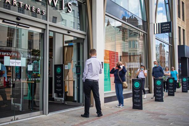 在英國切爾滕納姆的約翰·路易斯和合作夥伴商店外排隊的購物者在進入前戴上口罩,以説明阻止科維德19病毒的傳播。 - john lewis 個照片及圖片檔