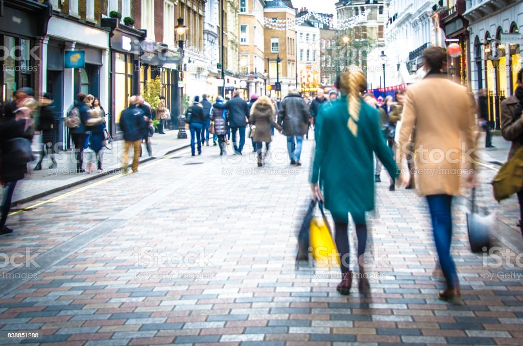 Shoppers walking down the high street holding hands and carrying shopping bags stock photo