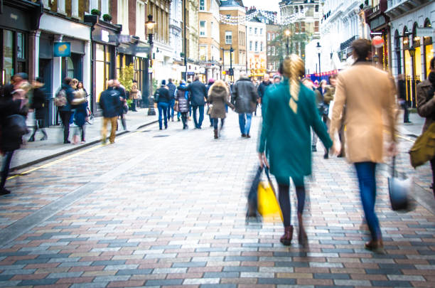 shoppers walking down the high street holding hands and carrying shopping bags - shopping stock photos and pictures