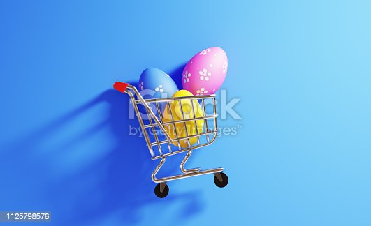 Colorful Easter eggs  in a shopping cart on blue background. Horizontal composition with  copy space. Shopping and Easter concept.