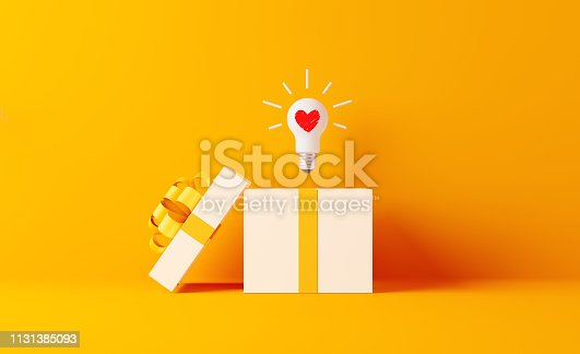 A light bulb with heart shape coming out of white gift box on yellow background. Horizontal composition with  copy space. Shopping and gift concept.