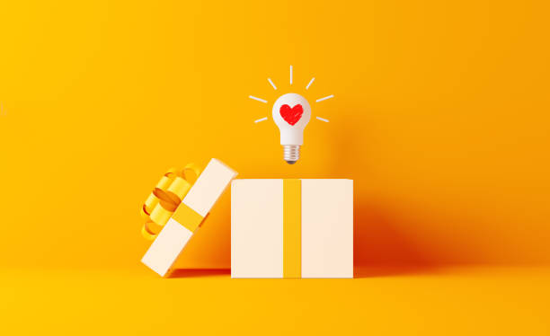 shopping and gift concept- a light bulb with heart shape coming out of white gift box - gift стоковые фото и изображения