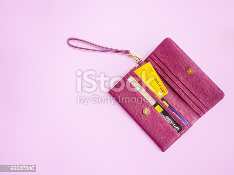 shopping and payment concept from red clutch purse on pink background with credit cards and discount cards in it. Closeup of modern red leather wallet. Top view on the wallet.