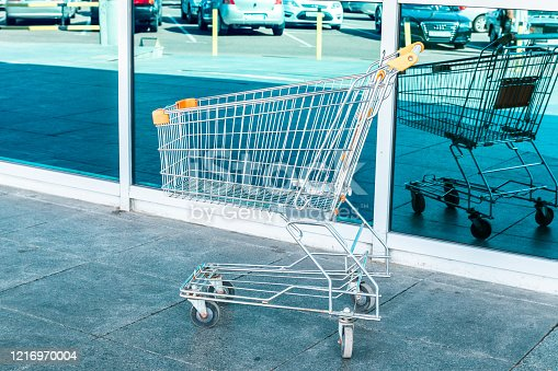 istock Shopping and store concept. A metal market cart stands near a glass building 1216970004