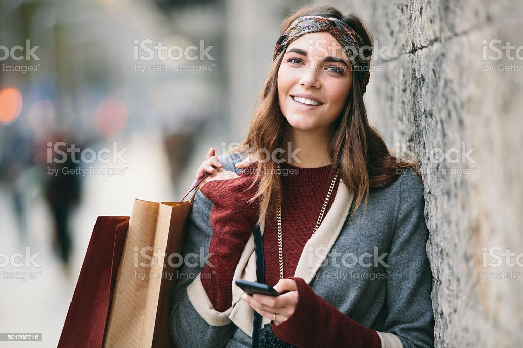 Shopping and texting on a winter day. stock photo