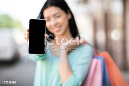 Online Shopping App. Asian Girl With Shopper Bags Showing Smartphone With Black Screen, Posing Outdoors, Mockup
