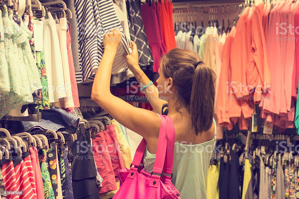 Young woman in retail store choosing clothes