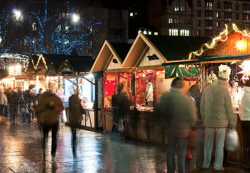 Long exposure blurring customers at a Christmas Market in Edinburgh, Scotland.