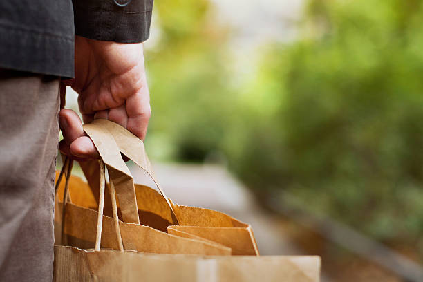 shopping background consumer basket, close up of paper shopping bags in male hand carrying stock pictures, royalty-free photos & images