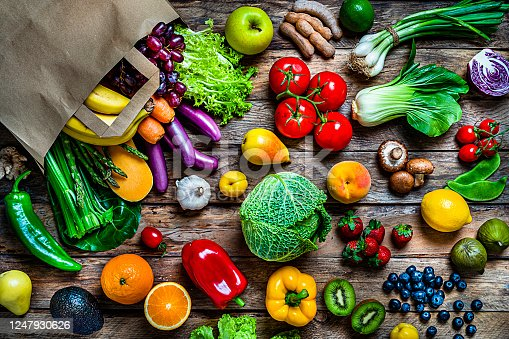 istock Shopping bag filled with fresh organic fruits and vegetables shot from above on wooden table 1247930626