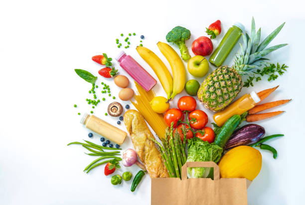 Shopping bag full of fresh vegetables and fruits isolated on white stock photo