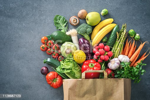 istock Shopping bag full of fresh vegetables and fruits 1128687123