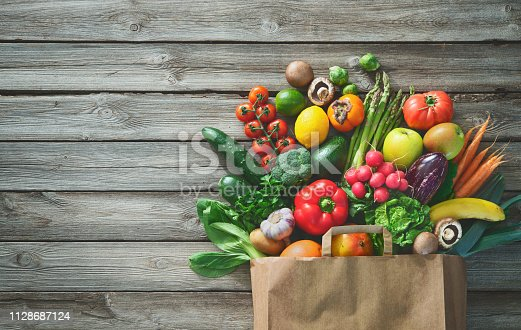istock Shopping bag full of fresh vegetables and fruits 1128687124