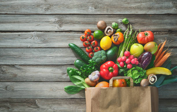 Shopping bag full of fresh vegetables and fruits Healthy food selection. Shopping bag full of fresh vegetables and fruits. Flat lay food on table and stock pictures, royalty-free photos & images