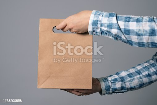A paper shopping bag in male hand isolated on gray background.