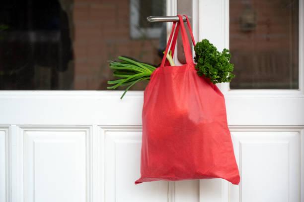 einkaufstasche mit waren und lebensmitteln hängt an der haustür, nachbarschaftshilfekonzept zur quarantänewegen wegen coronavirus-infektion, kopierplatz - standbildaufnahme stock-fotos und bilder