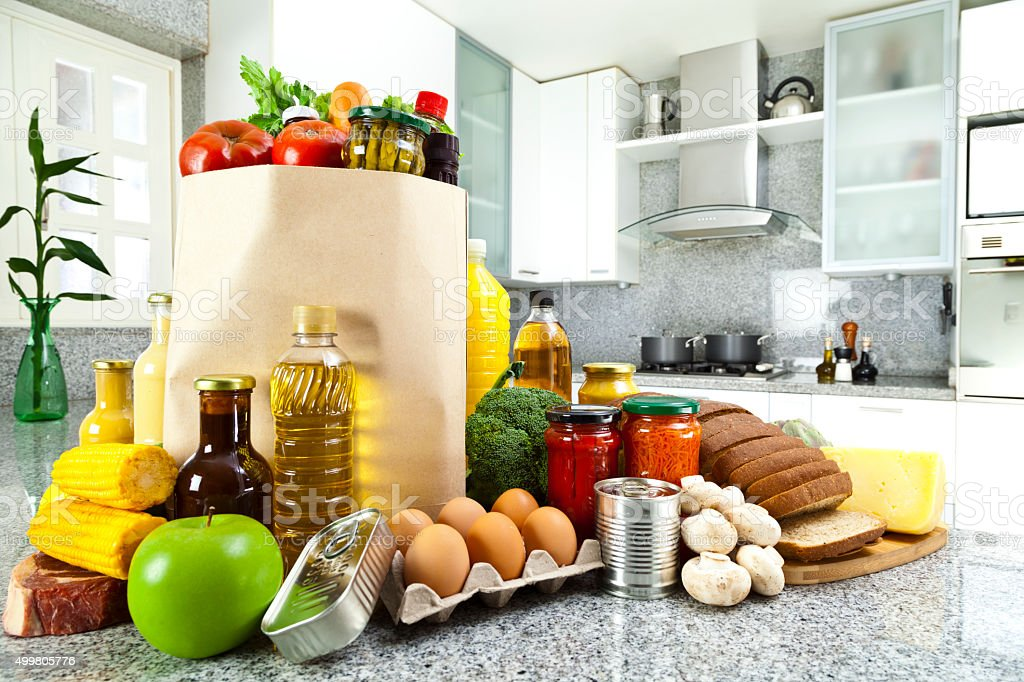 Shopping bag with groceries on kitchen countertop stock photo