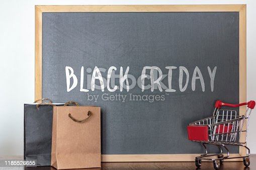 Shopping bags and trolley with blackboard on the background with the word Black Friday. Black Friday season sales concept