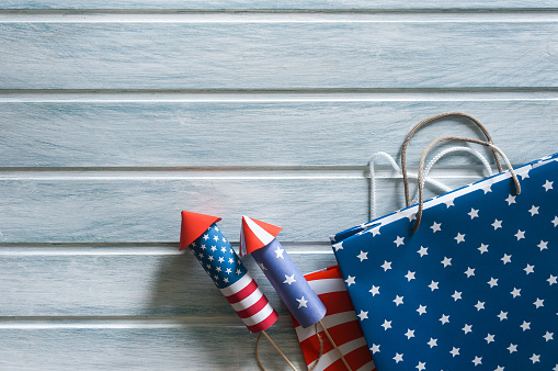 Shopping bags in national american colors and firework rockets