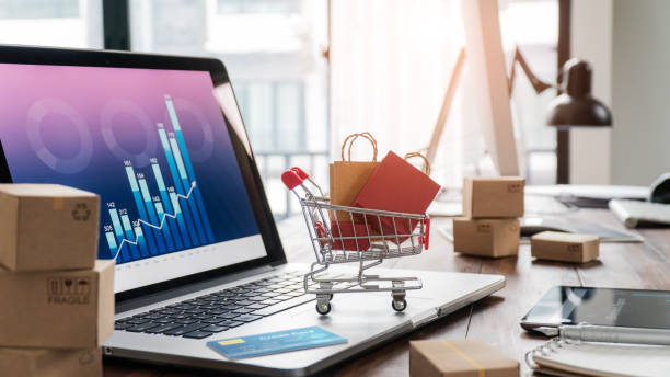 sacs à provisions dans le panier d'achat et carte de crédit sur ordinateur portable avec des boîtes en papier sur la table et les données de vente graphique de croissance économique à l'écran, l'achat et la vente de services en ligne sur le réseau, - graph photos et images de collection