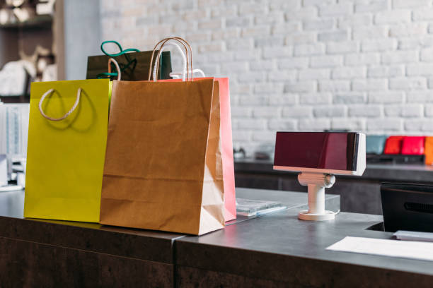 shopping bags standing on cash register in shopping mall, boutique shopping concept stock photo