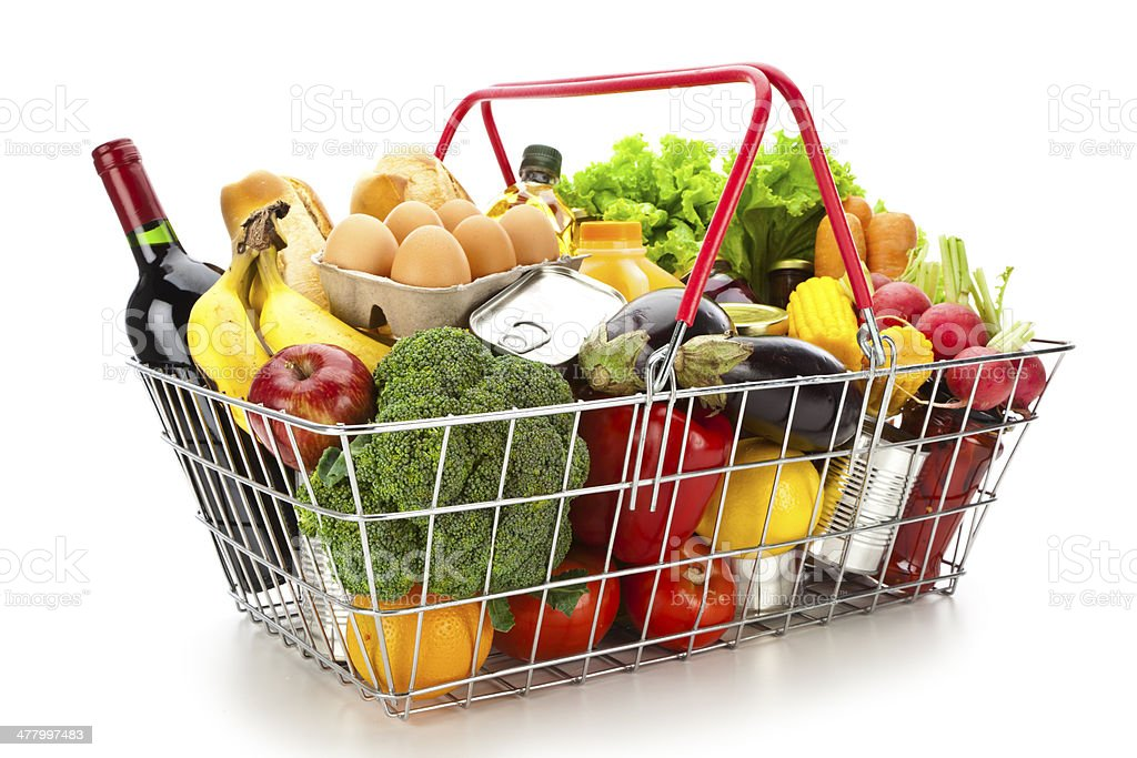 Shopping basket filled with colorful food against white backdrop stock photo