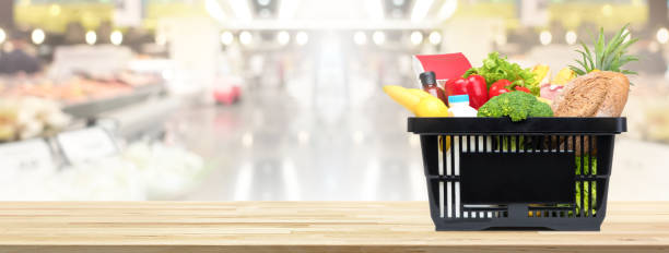 Shopping basket full of food and groceries on the table in supermarket stock photo