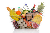 Wire shopping basket full of groceries including fresh fruit, vegetables, milk, wine, meat and dairy products. Isolated on a white background.
