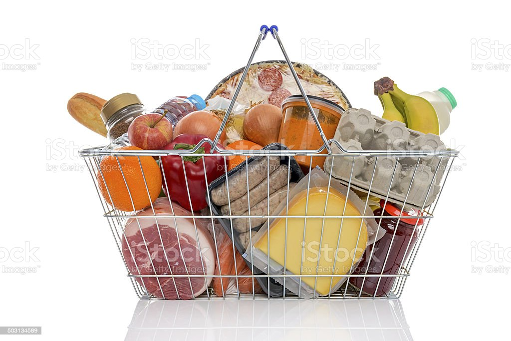 Shopping basket full of groceries isolated on white. stock photo
