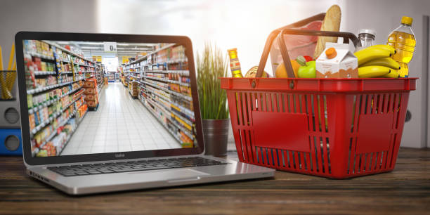 Shopping basket with food and laptop with shelf of supermarket  or grocery shop on the screen. Online ordering and delivery food concept. stock photo