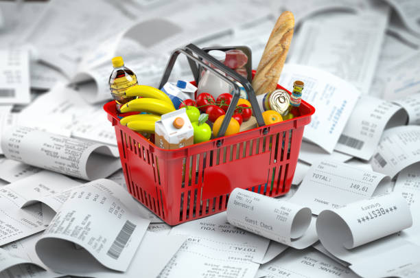 Shopping basket with foods on the pile of receipt.   Consumerism and grocery expenses budget stock photo
