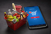 istock Shopping basket with fresh food and smartphone or mobile. Grocery supermarket, food and eats online buying and delivery concept. 1272245247