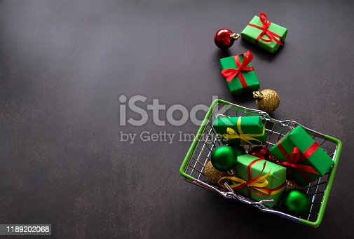 Shopping basket with gifts in green paper, red and yellow bows, Christmas balls of red, green, gold on a black background. Some gifts, balls lie near. Black Friday and sales concept. Copy space
