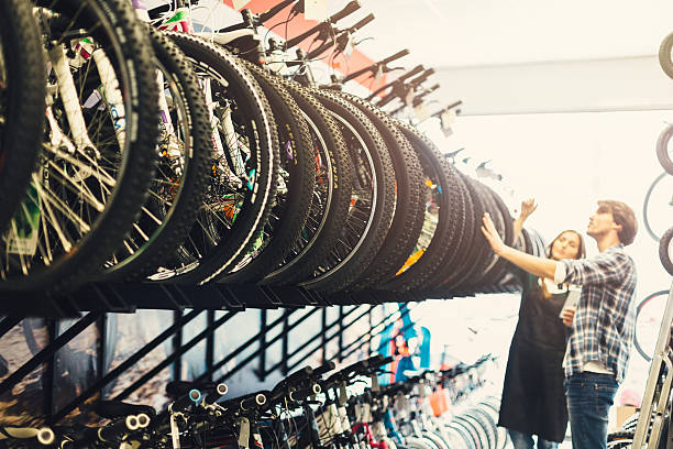 Shopping bike Young woman in bike store smiling at client bicycle shop stock pictures, royalty-free photos & images