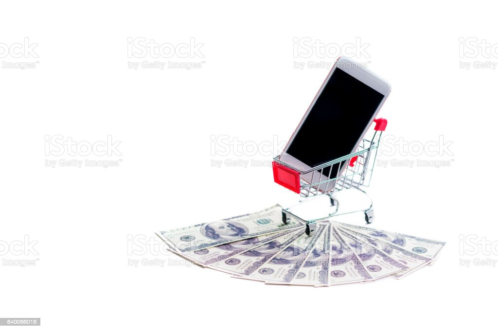 Shopping cart and dollars and smartphone stock photo