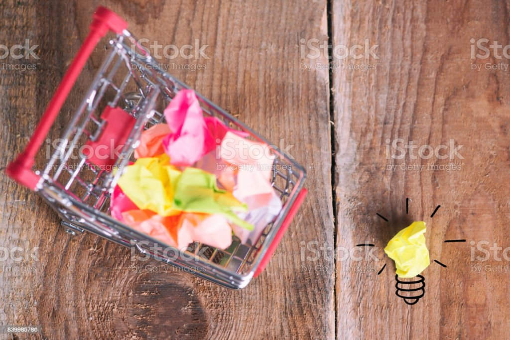 Shopping cart and small paper balls stock photo