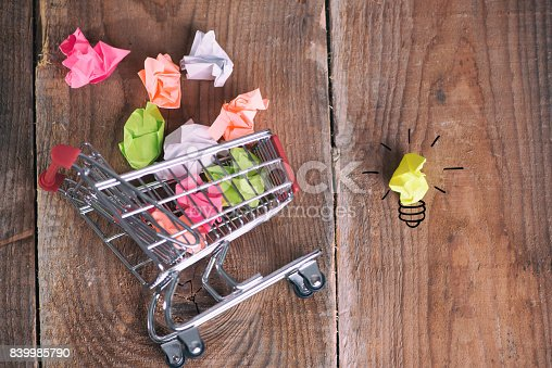 istock Shopping cart and small paper balls 839985790