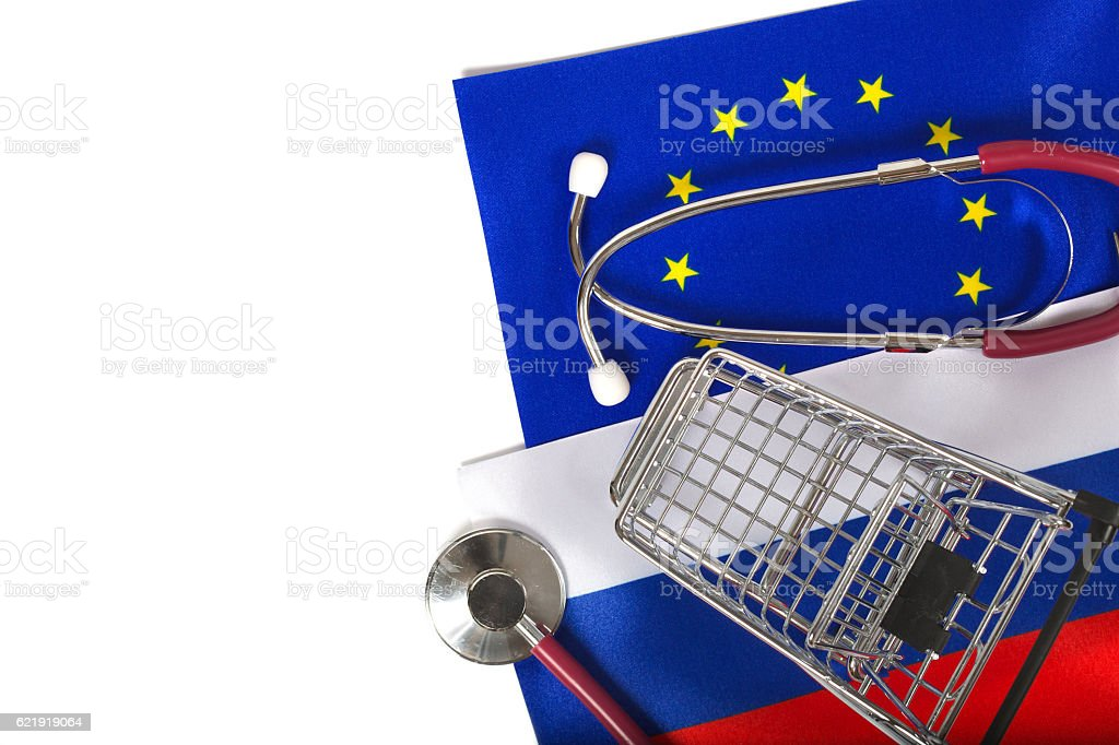 Shopping cart and stethoscope on European and Russian flags stock photo