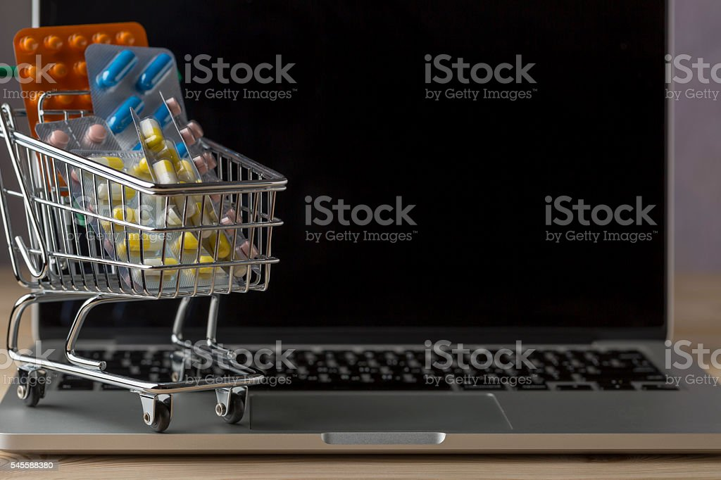 Shopping cart filled with blister on top open laptop stock photo
