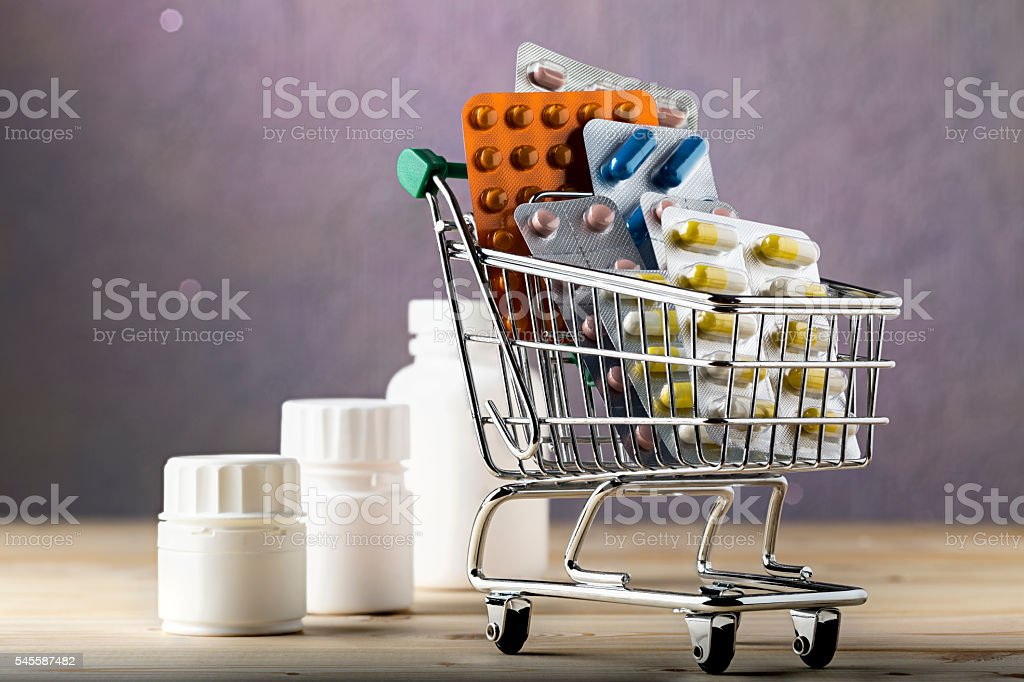 Shopping cart filled with blister packs of pills stock photo