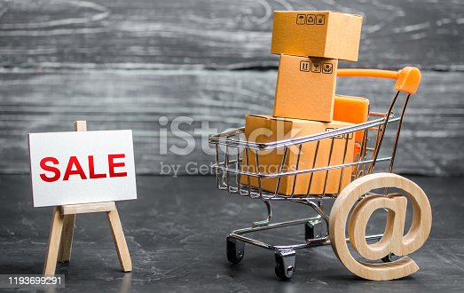 642250754 istock photo A shopping cart filled with cardboard boxes and an easel with the word Sale and email symbol. Advertising sale, marketing. Business strategy analysis. Discount. Shopping online. Attracting customers. 1193699291