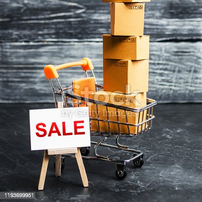 642250754 istock photo A shopping cart filled with cardboard boxes and an easel with the word Sale. Advertising sale, marketing. Business strategy analysis. Discount. Shopping online. Attracting customers at low prices. 1193699951