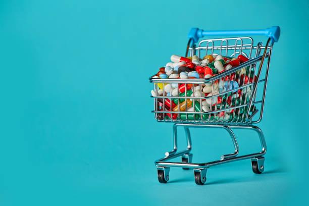 Carrito de compras lleno de pastillas. Fondo azul. Concepto: sistema completo de medicinas en la tienda. Copiar espacio para texto - foto de stock