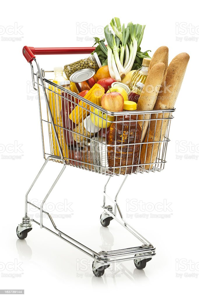 Shopping cart filled with variety of groceries on white backdrop stock photo