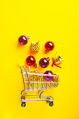 Shopping cart full of christmas balls, gifts and sparkling bells on a yellow background. New Year and Christmas concept.