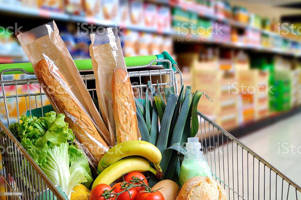 Carrito completo de alimentos en el supermercado pasillo elevado de vista - foto de stock